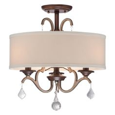 This Minka Lavery Gwendolyn Place ceiling semi-flush mount offers elegance for any ceiling. An oatmeal linen drum shade softens the light while smart crystal accents add sparkle. Dark rubbed sienna finish is accented with aged silver.