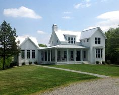 """Modern Farmhouse,"" with white board and batten siding, tall windows, and big…"