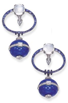 A PAIR OF ART DECO SAPPHIRE, MOONSTONE, ENAMEL AND DIAMOND EAR PENDANTS, BY GEORGES FOUQUET, CIRCA 1925. Each designed as a blue enamel boule, enhanced by diamond-set detail, to the calibré-cut sapphire oval top with demi-rondelle sapphire accents and central moonstone, signed G. Fouquet. #ArtDeco #Fouquet #earrings