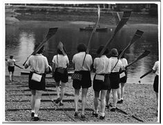 Women rowing crew carrying their oars down to the river with gas masks in boxes slung over their shoulders in London, 1939.