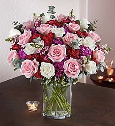 Victorian Romance™ Our elegant bouquet calls to mind the Victorian Era, when courtship and love were highly revered. Sweet pink and white roses, rich burgundy carnations and snapdragon and passionate purple dianthus are artfully hand-arranged in a sleek clear glass cylinder vase. It's a unique and sophisticated gift, sure to make your true love swoon!