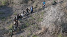 U.S. Border Patrol agents escort a group of undocumented immigrants into custody with helicopter support from the U.S. Office of Air and Marine on May 20, 2013 near the U.S.-Mexico border in Havana, Texas. (credit: John Moore/Getty Images)