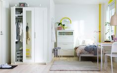 A small apartment with a wardrobe, chest of drawers, bed, small table and two chairs, all in white.