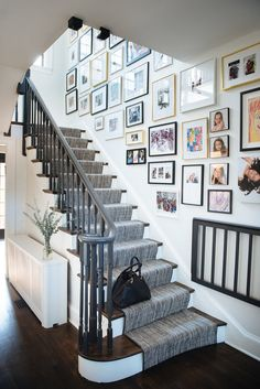 Photos line the wall along side a white staircase fitted with wood treads an a gray handrail complementing a gray stair runner. Staircase Wall Decor, White Staircase, Staircase Handrail, Staircase Design, Picture Wall Staircase, Black Stair Railing, Stair Art, Painted Staircases, Picture Walls