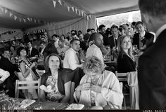 Wedding guests look at best man as he does his speech at River Cottage in a marquee. vintage bunting is seen decorating the room.