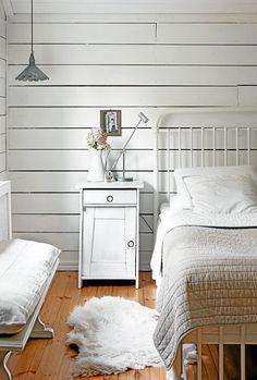 Kaijan valoisassa makuuhuoneessa on lakattu lattia. Rautarunkoinen sänky on perhetuttavan tekemä. Yöpöytä löytyi antiikkiliikkeestä.Leski sisusti kodistaan kauniin mummolan