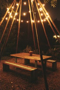tipi / teepee poles placed over picnic table, draped with lights, love this. You could even add mosquito netting. #outdoors #party #lighting