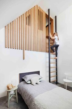 This modern kids bedroom has a loft area is reached via a ladder, with the loft partially hidden by wood slats.