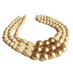 Three strands of faceted ivory painted wood beads, off-white rounds and painted gold wood beads create this thick bib necklace. Sits high like a collar. Big, bold, regal, and lightweight for its size.  Featured on the cover of Design Bureau's Weddings by Design.
