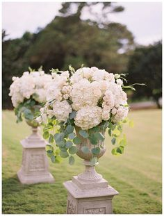 White flowers in tall urns. Florals by Bella Flora, image by Landon Jacob photographed at the Kiawah Island Club in South Carolina.