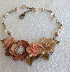 Flower Necklace.. A B'sue necklace blank was used for my focal piece, I used Diamond Glaze on the Flowers to harded them & a dusting of Perfect Pearls on top of each flower, a few B'sue leaves used along with a few from my stash, B'sue Brass Chain, Pearls and Glass Clear Beads are in the chain .. https://www.facebook.com/JewelsByJann .. FOR SALE
