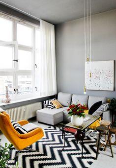 vintage style apartment of stylist Boris Zbikowski, yellow lounge chair, wooden stools, graphic rug