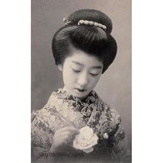 A young woman in kimono and traditional Japanese hairstyle looks at a white rose she holds. This postcard was published sometime between 1907 and 1918. During the early 20th century, picture postcards of bijin (beautiful women) were extremely popular in Japan.