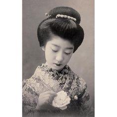 昔からの髪型の着物姿の女性が、手に持った薔薇を見つめている。この絵葉書が出版されたのは1907年から1918年頃である。20世紀初頭、美人の写真絵葉書は大変人気があった。