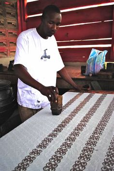 West African Adinkra printing - A man using a stamp to print onto fabric