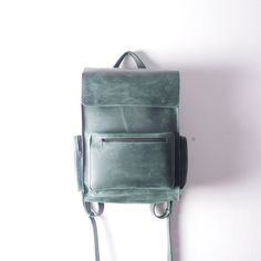 Handmade Green leather backpack made from cowhide leather of vintage style  - One roomy compartment ( fits Laptop 15) - one slip pocket inside (18cm * 15cm) - strap width 2,7 cm - main compartment closes on snap buttons - one front zipper pocket 25 * 17 * 3cm (9,8 * 6,7 * 1,2 in) - two zipper pockets on sides 8 * 17 * 3 cm ( 3,15* 6,7 * 1,2 in) Available to order in black, gray, red, brown, dark blue, orange and green colors.  DIMENSIONS:  Height: 40 cm / 15,7 in Width: 30 cm / 11,...