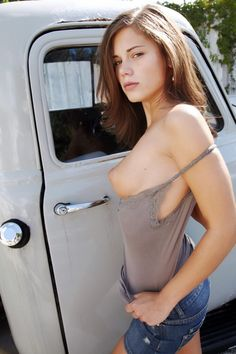 sexy girl exposing her breast next to a classic truck 画