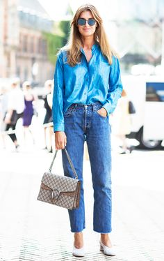 A blue button-down shirt is tucked into raw hem jeans, and worn with gray suede pumps, a Gucci bag, and mirrored sunglasses