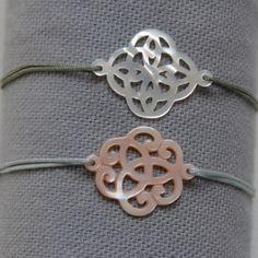 Bracelet arabesque en nacre monté sur lien fin satiné, ajustable.