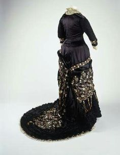 Dress, C. Appin. Silk satin with panels of machine embroidery, cotton machine lace and silk fringe. 1878-1882.