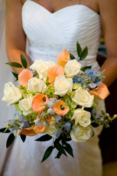 Orange and green are beautifully complemeted with cream and blue in this bride's bouquet.