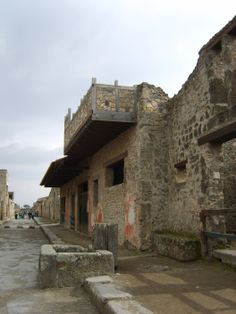 Example of a typical Roman street from Pompeii.  Notice the house and shop frontages are built right onto the pavement, upper storeys overhang, the high pavement curb with large curbstones, the large stepping stones crossing the street, grooves in the road caused by the wheels of horses and carts, and the fountain in the foreground.