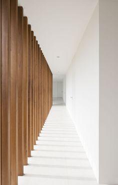 Un mur filtre modulant la lumière du jour et l'intimité.  Le bois mis en valeur dans un décor tout blanc.