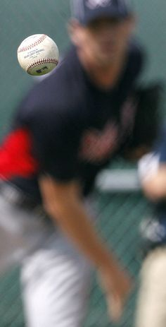 A ball thrown by Atlanta Braves pitcher Cory Gearrin makes its way to catcher David Ross during spring training baseball, Thursday, Feb. 23, 2012, in Lake Buena Vista, Fla. (AP Photo/Julio Cortez)