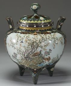 A large tripodic cloisonné censer worked in colored enamels and silver wires. On one panel, cranes cluster among bamboo in pastel hues against a pale green ground; on the other, pheasants and plovers under flowering sakura appear against a delicate blue ground. Marvelous scrollwork, geometric forms and kiku cover all remaining areas, including the bottom, reticulated lid and knop. Height, 10; width, 7.5. Attribution: Hayashi Kodenji. Meiji Period.