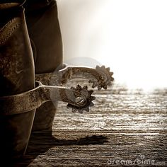 American West rodeo cowboy traditional leather boots with authentic western riding spurs on old weathered wood planks at sunset