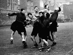 Bob Paisley jumps for a header with teammates, including the legendary Billy Liddell, during a kick-about in the Anfield car park