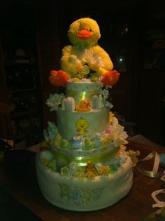 "Duck themed gender neutral diaper cake, includes; 112 size 2 diapers, 3 flannel receiving blankets, 1 30""x40"" soft blanket, plush duck, three rubber duck bath toys, a 4 piece layette set (outfit, bib, cap & booties), 1 footless sleep and play outfit, 3 onesies, 3 pairs of socks, 4 washcloths, a 9 oz bottle, 2 pacifiers and a clip, J travel kit, brush and comb, nail set, outlet covers and a bottle brush"