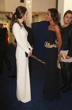 """Naomie Harris and Catherine, Duchess of Cambridge, aka Kate Middleton, attending the premiere of the film """"Mandela: Long Walk to Freedom"""" in London. Kate is wearing the """"Lombard"""" gown by Roland Mouret, Zara's Sparkly Crystal Bead Necklace, black suede pumps possibly by Prada, and clutch possibly by Mulberry. 12/05/13"""