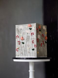 Square cake decorated with a concrete effect buttercream and a+r signature floral work