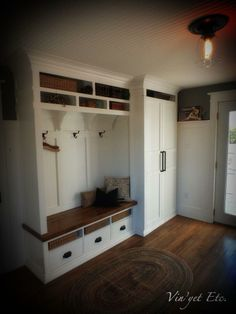 Use a tall cabinet next to bench area to store vacuum and brooms, ironing board.