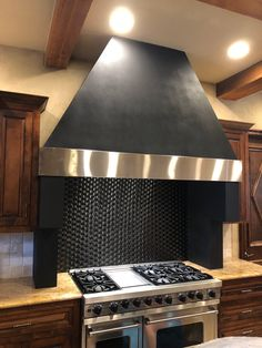 This beautiful custom handcrafted vent hood features a textured paint finish with a stainless steel trim band. In addition to the vent hood, Beach Sheet Metal also fabricated and installed the corbels below the hood.  #venthoods #luxurykitchens #customkitchens #interiordesign #elegantdesign #interiorarchitecture #handmadeventhoods  #dreamkitchen #beachsheetmetal