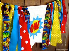 Superhero Birthday Banner Highchair High Chair Super Hero Red Blue Yellow One First Birthday Comic Party Super Star Cake Smash Photo Prop by SeacliffeCottage ️Comic book super hero themed ONE Birthday Banner with Rag Tie Garland Canvas double layered flag with hand cut applique and number. Fabric print rag ties in blue, yellow and red accent the banner. Would you like two instead of one? I can customize your banner to match your little ones special day.  This bunting is perfect when hung on…