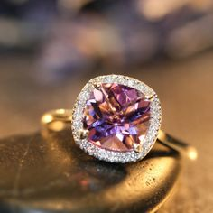 This halo diamond and amethyst ring features a 8x8mm cushion cut natural purple amethyst surrounded by sparkling conflict free diamonds set in a
