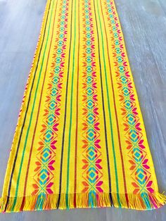 Beautiful folkloric Mexican colorful embroidered yellow table runner! Great for your next Mexican themed party or Fiesta! Great quality fabric from Mexico. The ends have fringes for a more traditional