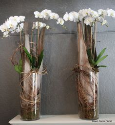 Display on back wall. Orchids in tall vases with palm fronds.