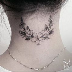 Flower wreath tattoo on the back of the neck.