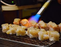 Aburi searing on the table  | Hotate (Scallop) & Salmon Oshi Sushi  by jacquelinechui
