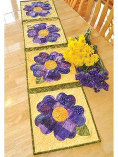 """Celebrate spring year-round! This blooming and stunning table runner is perfect for placing on your kitchen table year-round to celebrate the beauty of spring. A great way to use up scraps, this applique pattern can be made in any color to highlight any season -- from browns and oranges for autumn to purples and greens for spring. Finished runner size is 12 1/2"""" x 53""""."""