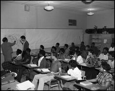 Date: February 11, 1959 Creator: Douglass, Neal Description: Photograph of a classroom of coed, African-American students at the old Anderson High School in Austin, Texas. On the left, a student and teacher study a map of the United States with the major rivers emphasized while the rest of the students, who are seated at their desks, look on. Contributing Partner: Austin History Center, Austin Public Library