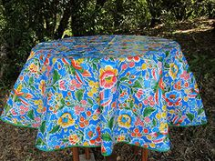 Round Primavera On Blue Mexican Oilcloth Tablecloth In A Wooded Area