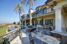 Dream home caliber backyard with great views and cool inground pool, and inviting large custom made travertine patio with brown patio furniture.