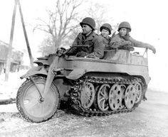"""US sappers of the 327th Battalion, 102nd Infantry Division on captured German half-track motorcycle """"Kettenkrad» (Kettenkrad HK 101) Besvaylere, Germany. From left to right: Corporal Henry Banas, Sergeant John Lewis and Private Everett Turk."""