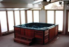 Indoor hot tub with fireplace TV in a room with a door leading to a pool n desk…