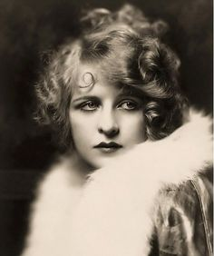 Ziegfeld girl Myrna Darby shows off a stylish curly bob and lips with a heavily exaggerated Cupid's bow. One of the quickest ways to suggest Prohibition-era glamour is to overemphasize this little dip at the top of your lips.