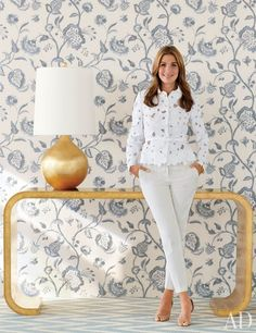 <3 lamp and table! | Cosmetics executive turned home-furnishings designer Aerin Lauder stands with some star pieces from her new Aerin collections: the Edgewood gilded console table, a Warren gilt-finish table lamp, Noyak embroidered linen blend (on the wall), and a Holly handmade wool dhurrie.